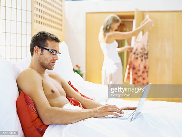 Portrait of a young man in bed working on a laptop with a young woman in the background.