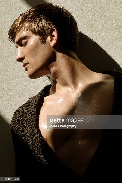 Portrait of a young man leaning on a wall in the sunlight