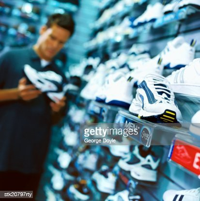 portrait of a young man looking at shoes in a shoe store : Stock Photo