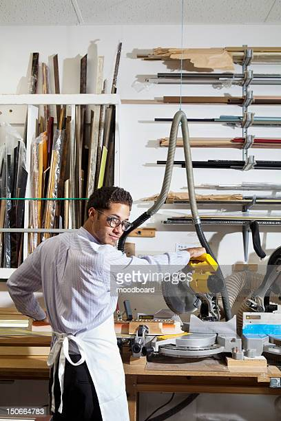 Portrait of a young man looking back while using circular saw in workshop