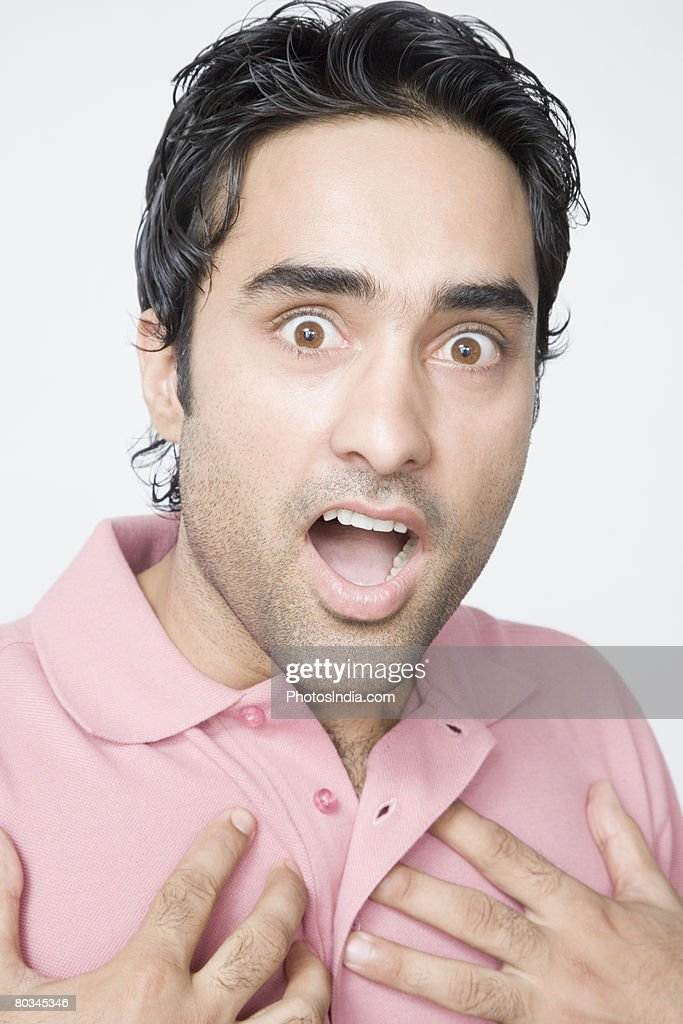 Portrait of a young man looking surprised : Stock Photo