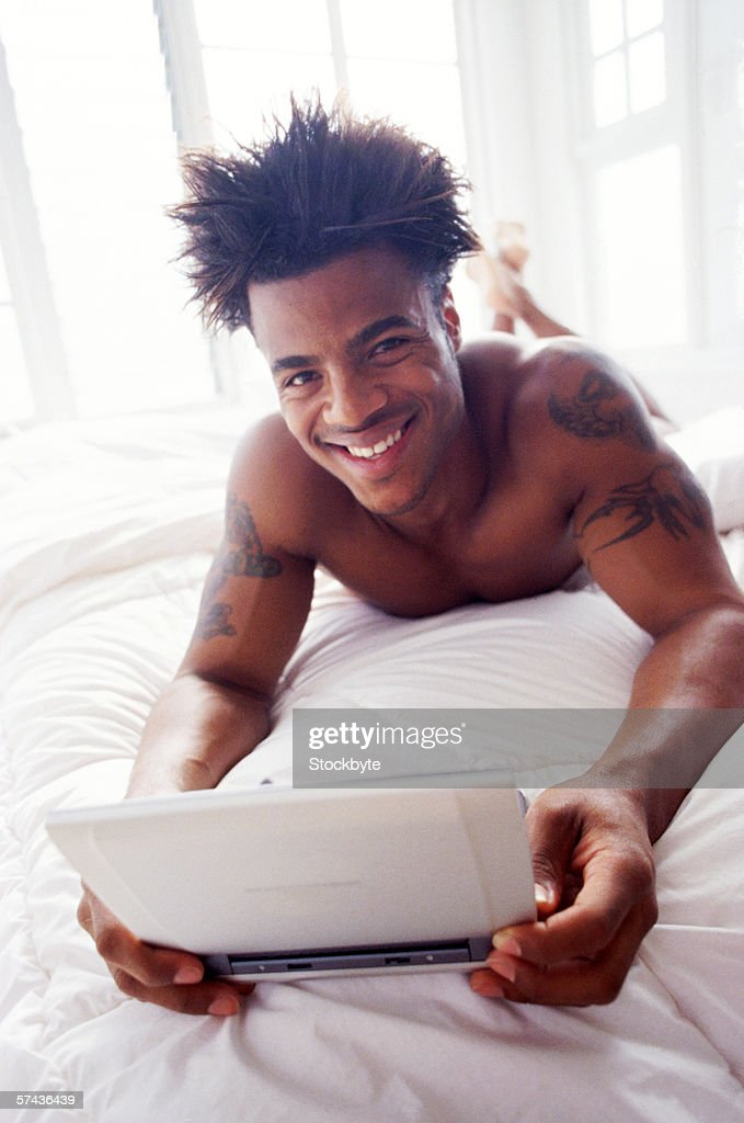 portrait of a young man lying on a bed and holding a laptop in his hands : Stock Photo