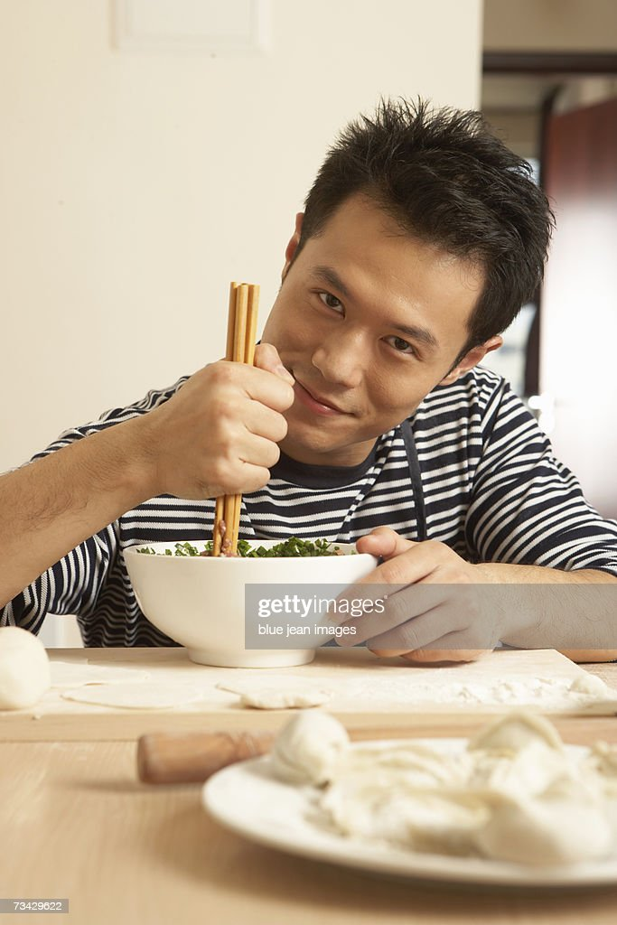 Portrait of a young man pausing as he mixes the fillings for a meal of traditional Chinese dumplings. : Stock Photo