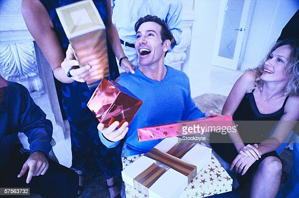 portrait of a young man receiving gifts from his friends