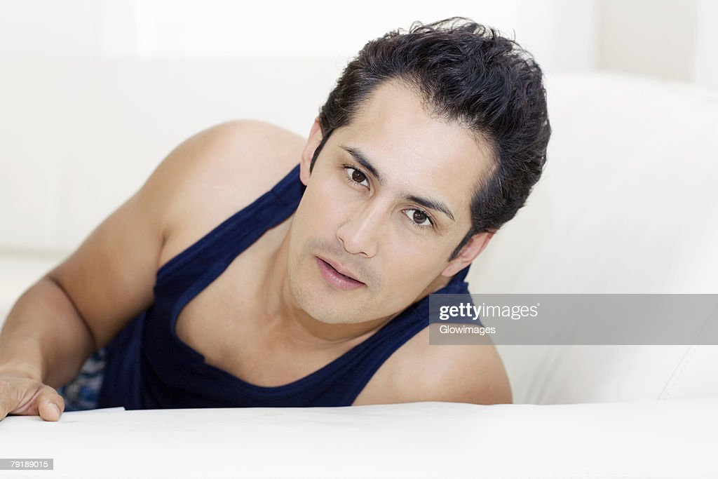 Portrait of a young man reclining on a couch : Stock Photo