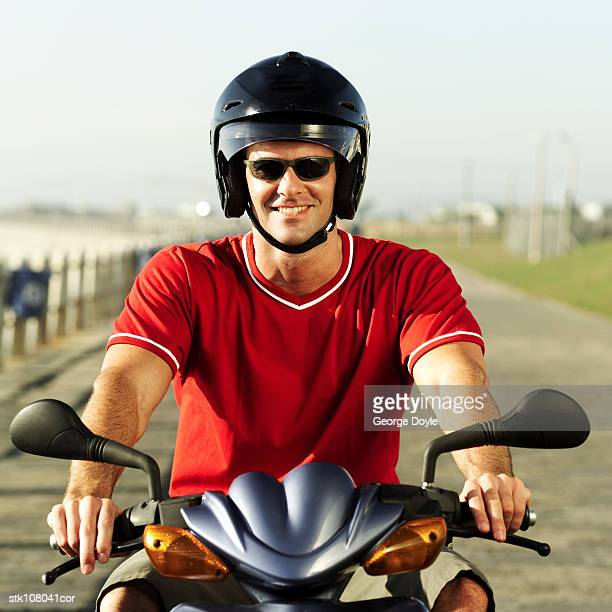 portrait of a young man riding a motor scooter