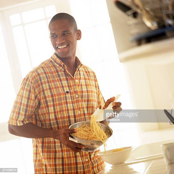 portrait of a young man serving spaghetti from a bowl