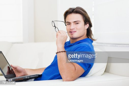 Portrait of a young man sitting in front of a laptop and holding eyeglasses : Foto de stock
