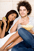 Portrait of a young man sitting with a young woman holding a bowl of popcorn