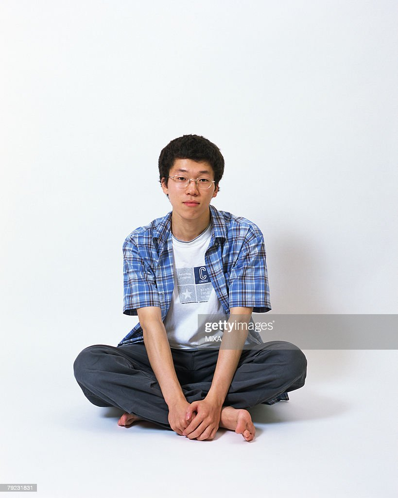 Portrait of a young man sitting with his legs crossed : Stock Photo