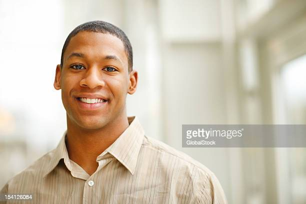 A portrait of a young man smiling at a camera