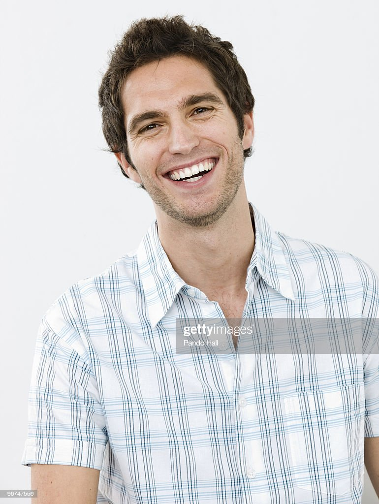 Portrait of a young man smiling, close-up : Stock Photo