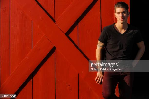 Portrait of a young man standing against a red barn door