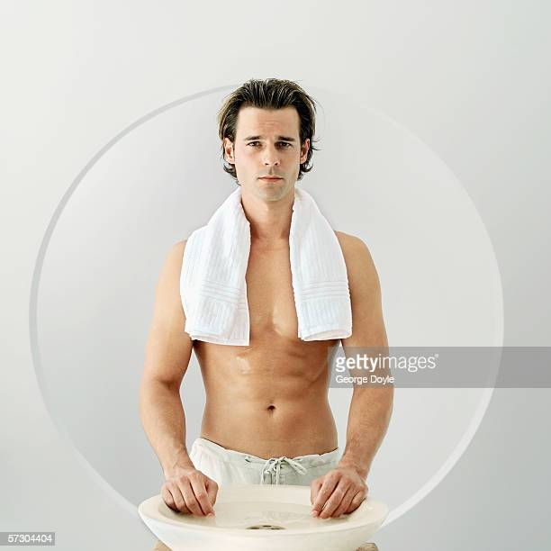 Portrait of a young man standing at a wash basin with a towel around his neck