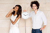 Portrait of a young man standing near a clock with a young woman talking on a mobile phone