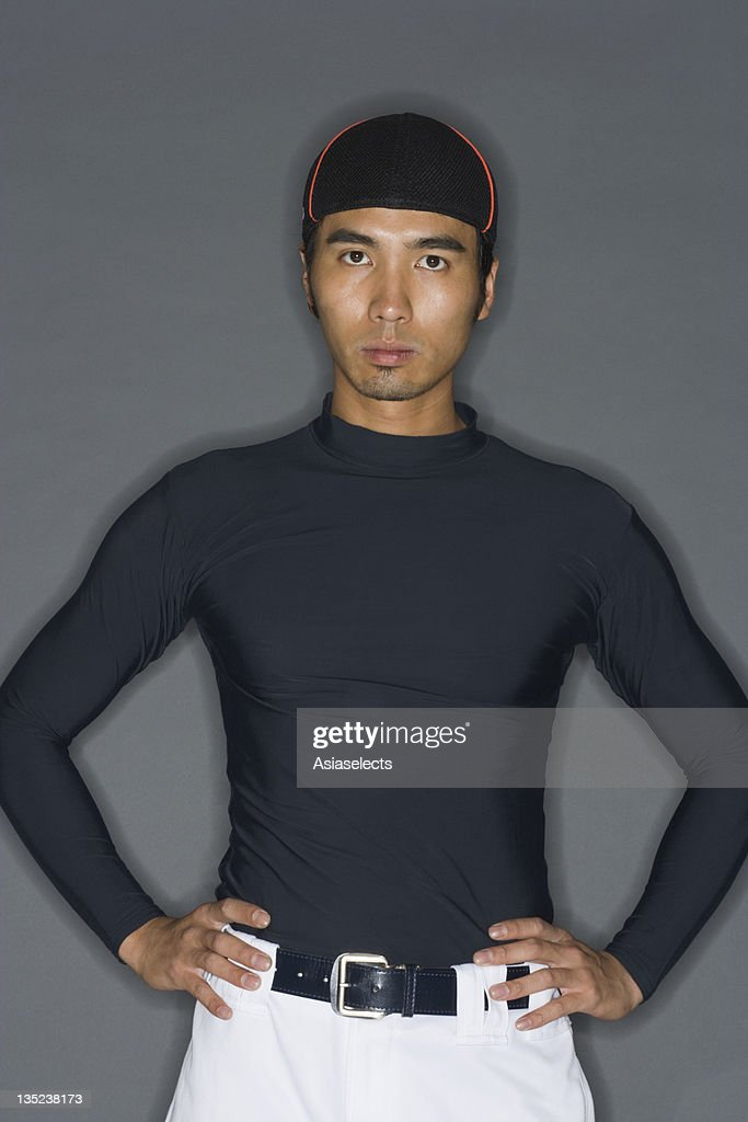 Portrait of a young man standing with arms akimbo : Stock Photo
