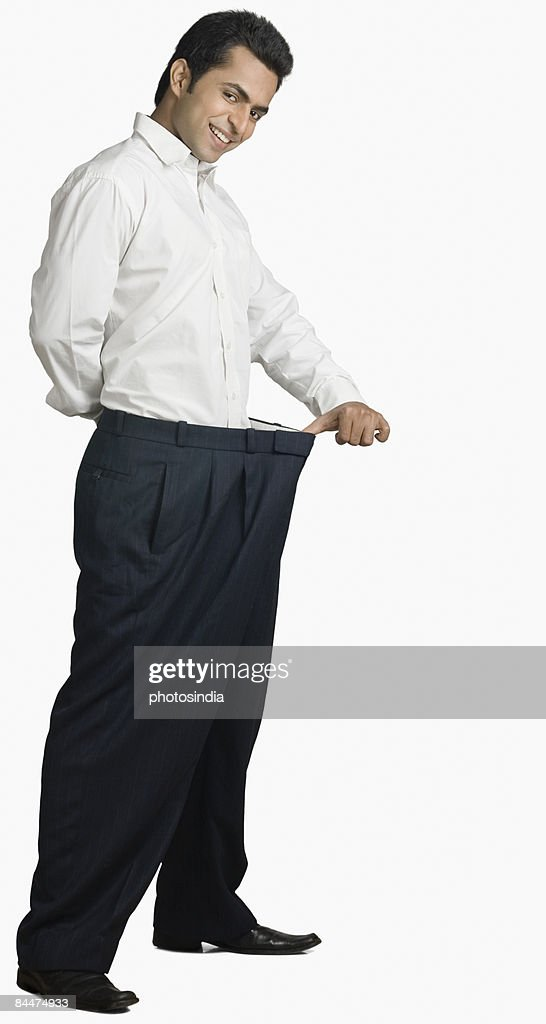 Portrait of a young man stretching his pant and smiling