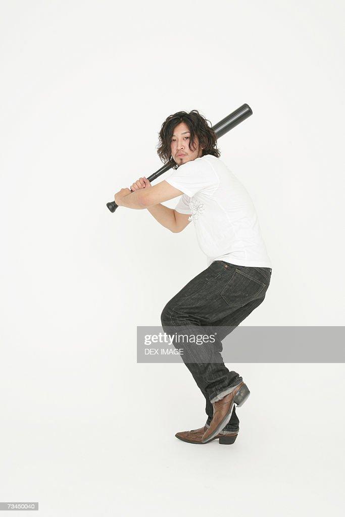 Portrait of a young man swinging a baseball bat