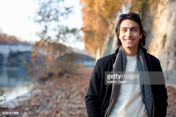 Portrait of a young man taking a walk along the riverbank, Rome, Italy
