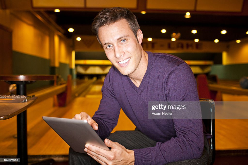 Portrait of a young man using a tablet device. : Stock Photo