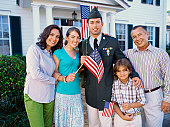 Portrait of a young man wearing a military uniform and his family