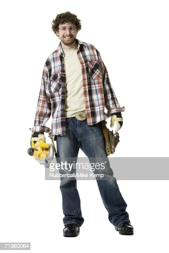 Portrait of a young man wearing a tool belt and holding a circular saw