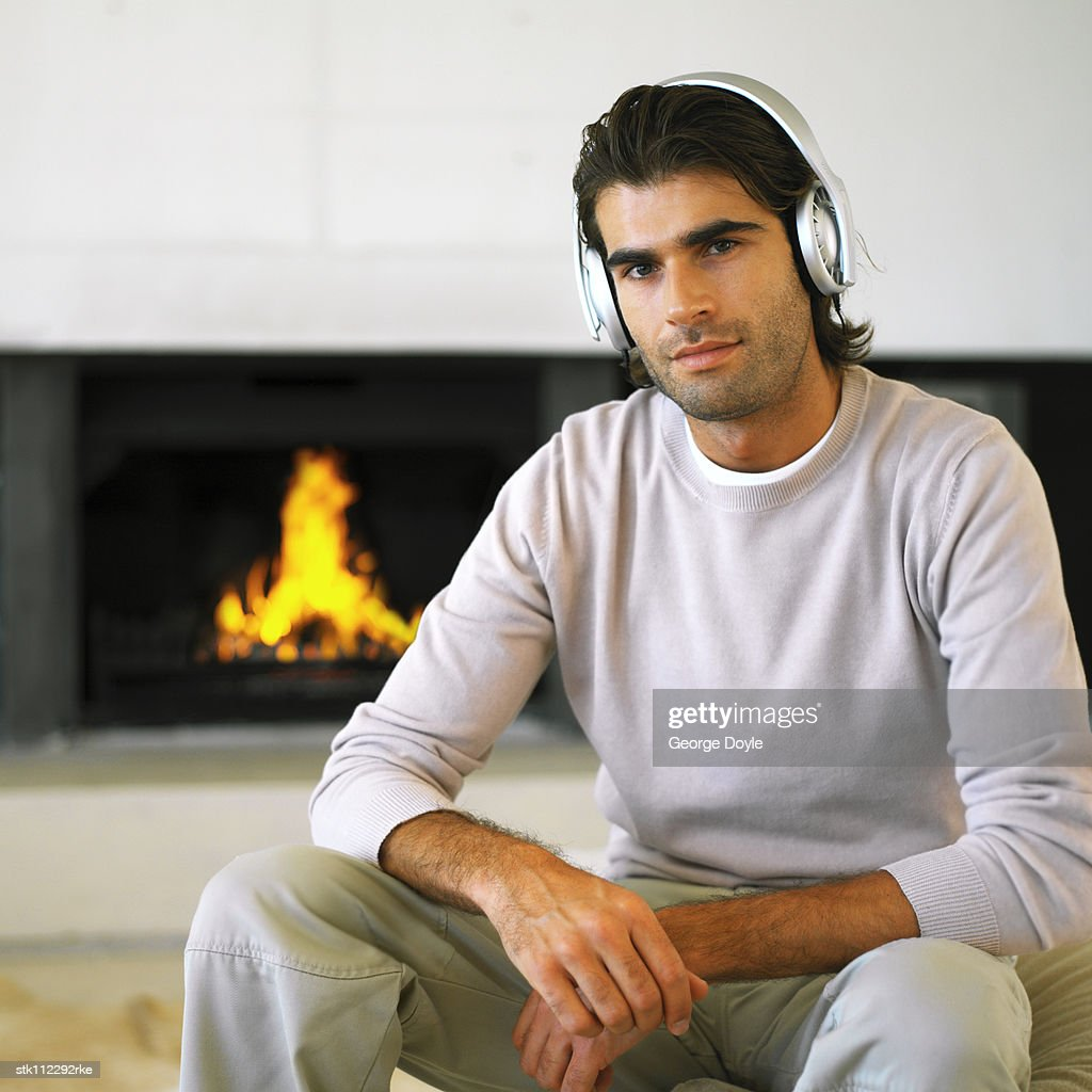 portrait of a young man wearing headphones sitting in front of a