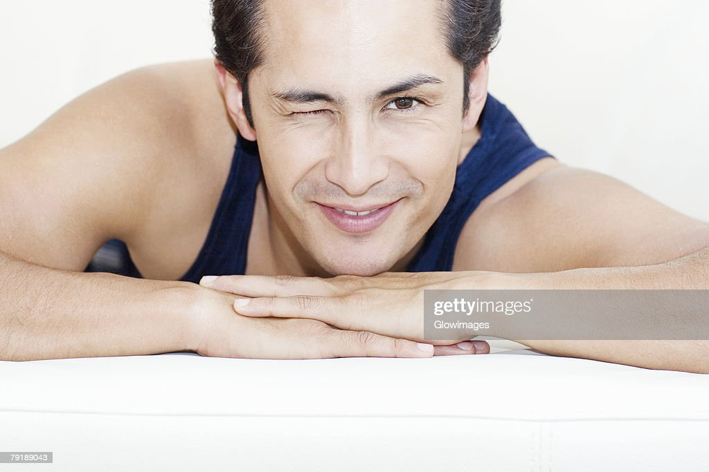 Portrait of a young man winking his eyes and smiling : Foto de stock