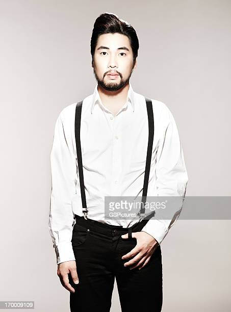 Portrait d'un jeune homme avec bretelles regardant la caméra
