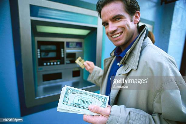 portrait of a young man withdrawing money at an automatic transaction machine