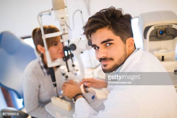 Portrait d'un jeune optométriste avec une patiente