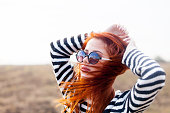 Portrait of a young redhead girl in sunglasses and striped sweater at outdoor in autumn time