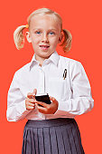 Portrait of a young schoolgirl holding cell phone over blue background