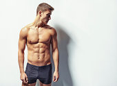 Portrait of a young sexy muscular man in underwear looking away against white wall with copy space