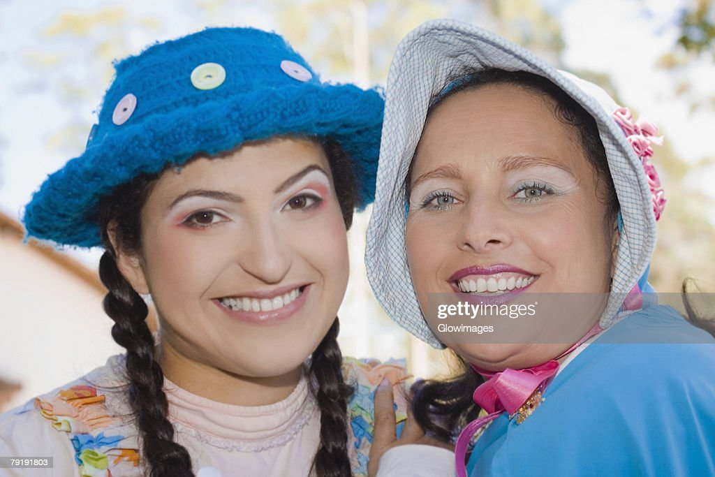 Portrait of a young woman and a mid adult woman smiling : Stock Photo