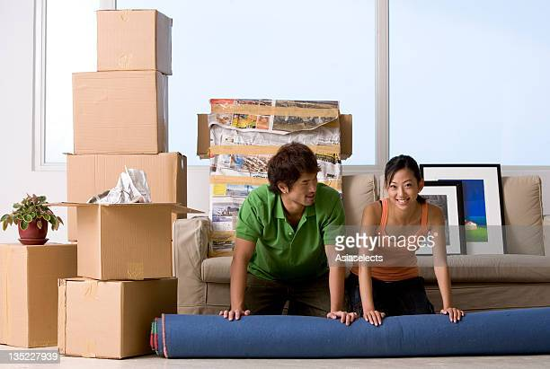 Portrait of a young woman and a young man rolling out a carpet on the floor