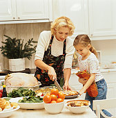portrait of a young woman and her daughter (10-12) preparing a thanksgiving meal