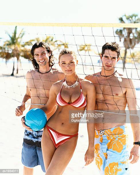 Portrait of a Young Woman and Men in Swimwear Standing by a Volleyball Net