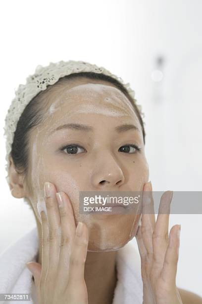 Portrait of a young woman applying soap on her face