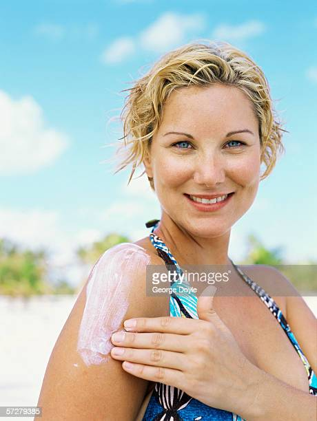 Portrait of a young woman applying sun block on her shoulder