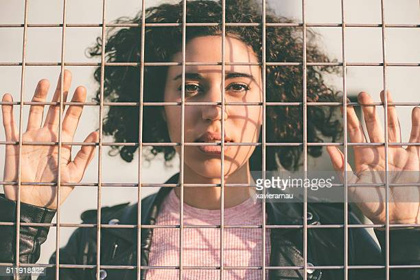 Portrait of a young woman behind a wire mesh
