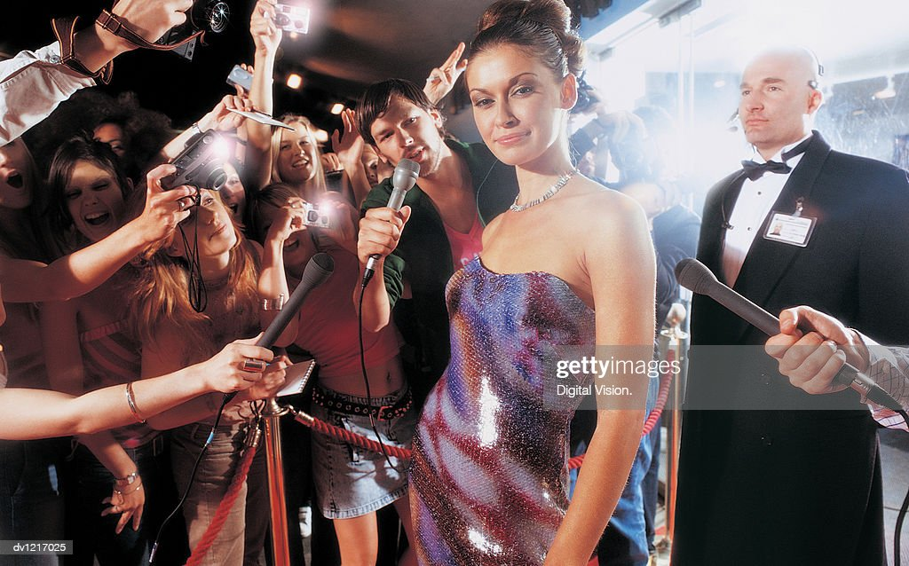 Portrait of a Young Woman Being Photographed by Paparazzi at Night : Stock Photo