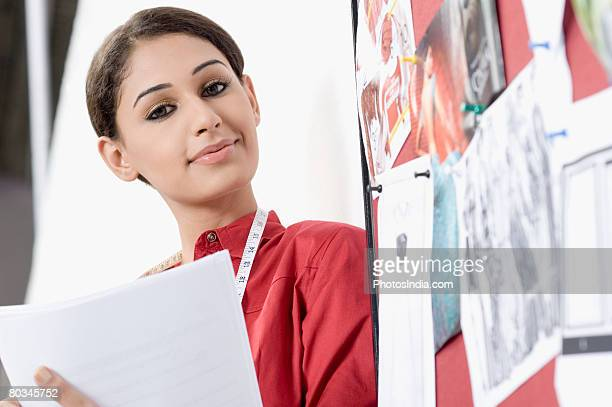 Portrait of a young woman beside a mood board and smirking