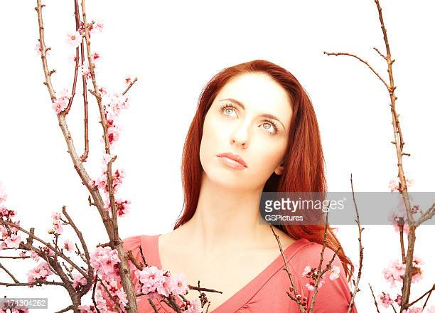 Portrait of a young woman between branches with pink flowers
