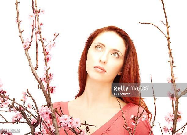 Portrait d'une jeune femme avec des fleurs roses entre les branches