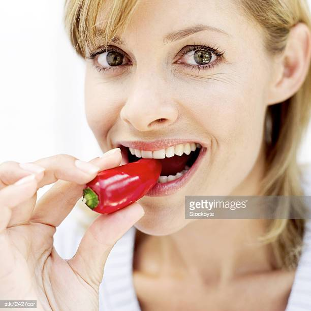portrait of a young woman biting into a red pepper