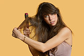 Portrait of a young woman brushing hair over colored background