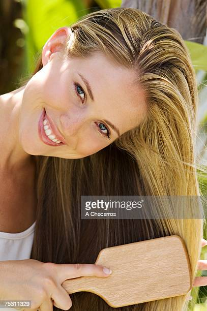 Portrait of a young woman brushing her hair, outdoors