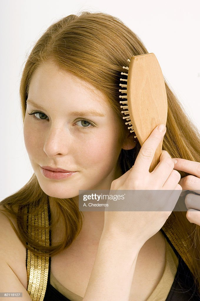 Portrait of a young woman brushing her hair : Stock Photo