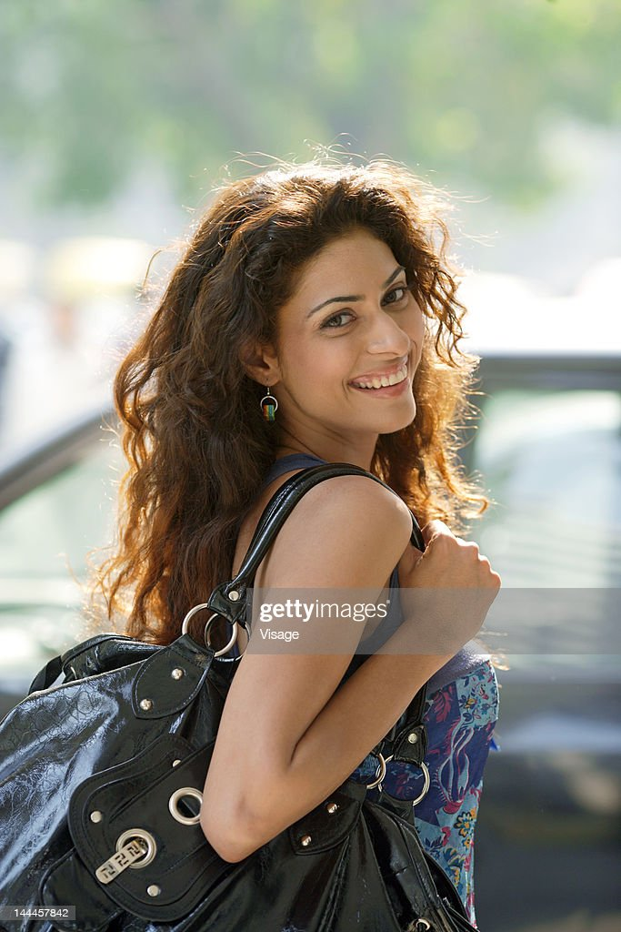 Portrait of a young woman carrying shoulder bag : Stock Photo